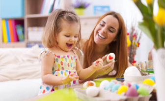 teacher and little girl paiting a heart on egg shell